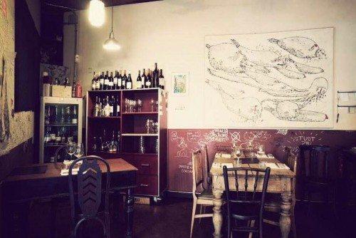 La sala…mesas desnudas, madera, paredes decoradas y buenos vinos a la vista….